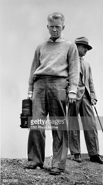 Low angle view of future American businessman and CBS president Frank Stanton as he stands on a rocky terrain and holds a still camera late 1920s An...