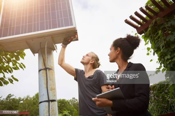 Low angle view of garden architect adjusting solar panel by colleague holding tablet computer