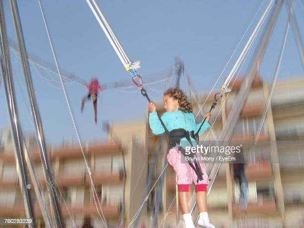 Low Angle View Of Girl Enjoying Bungee Trampoline