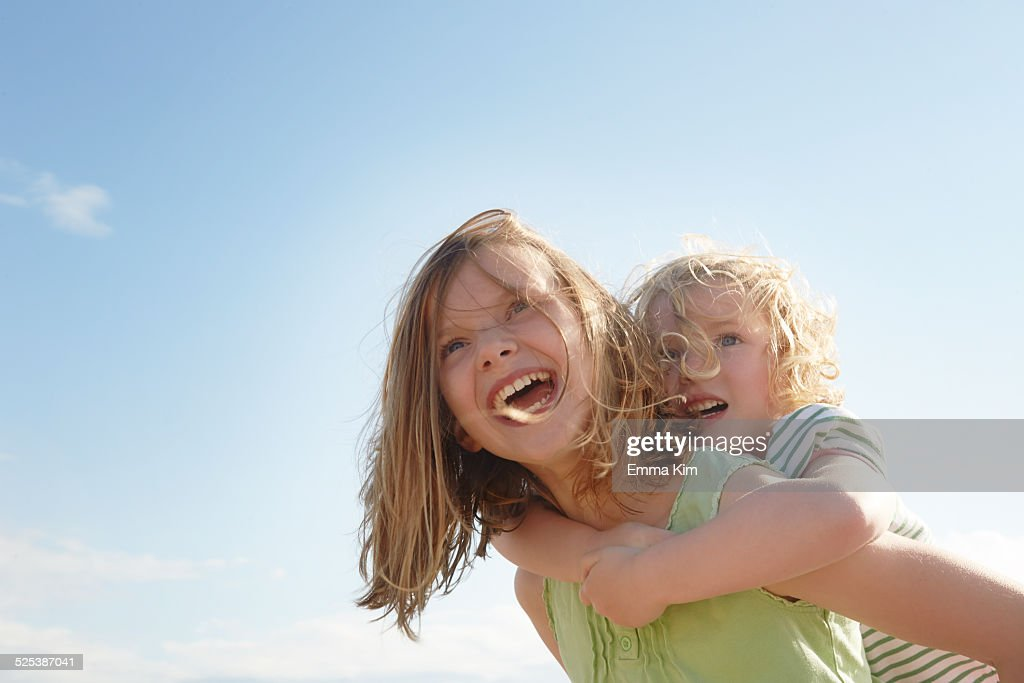 Low angle view of girl giving sister piggy back at coast