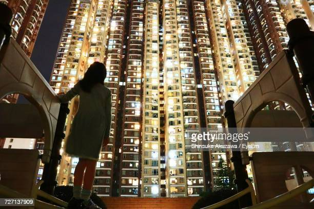 Low Angle View Of Girl Looking At Skyscraper