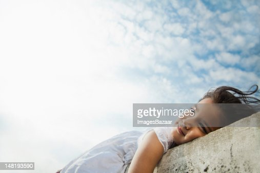 Low angle view of girl (6-7) lying on wall against sky : Stock Photo