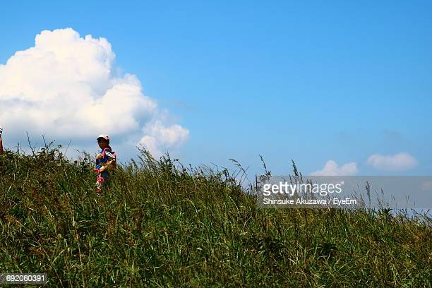 Low Angle View Of Girl Standing On Grassy Hill Against Sky