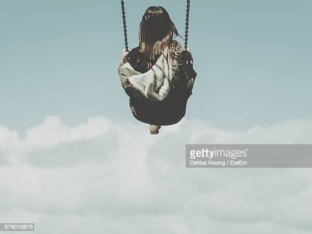 Low Angle View Of Girl Swinging Against Cloudy Sky