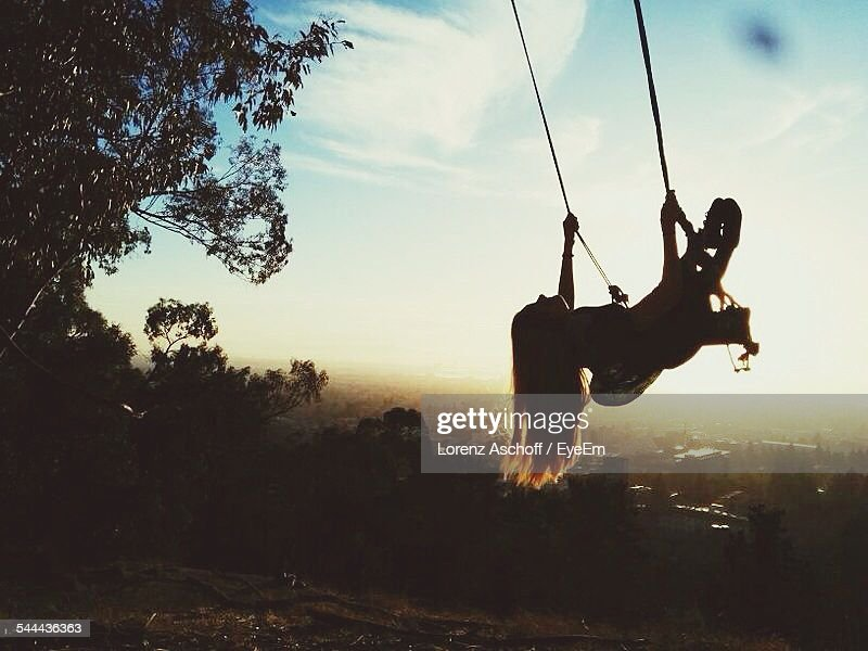 Low Angle View Of Girls Swinging In Park During Sunset : Stock Photo