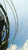 Low Angle View Of Globe Sculpture With Airplane In Sky At Flushing Meadows Park
