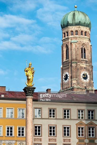 Low Angle View Of Gold St Marys Statue Against Frauenkirche Tower In Marienplatz