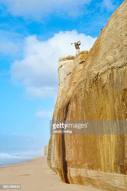 Low angle view of golfer on cliff top overlooking beach taking golf swing