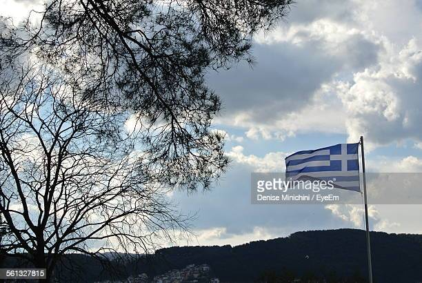 Low Angle View Of Greek Flag Waving Against Mountains