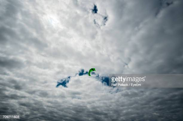 Low Angle View Of Green Kite In Cloudy Sky