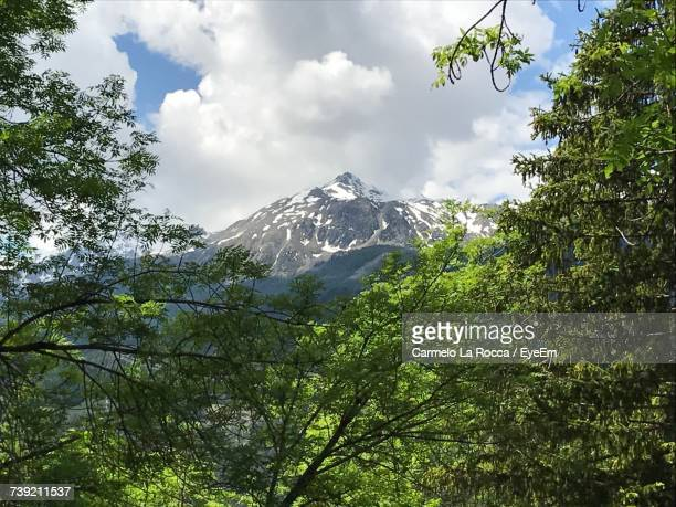 Low Angle View Of Green Mountains Against Cloudy Sky