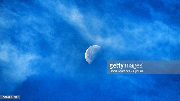 Low Angle View Of Half Moon In Blue Sky