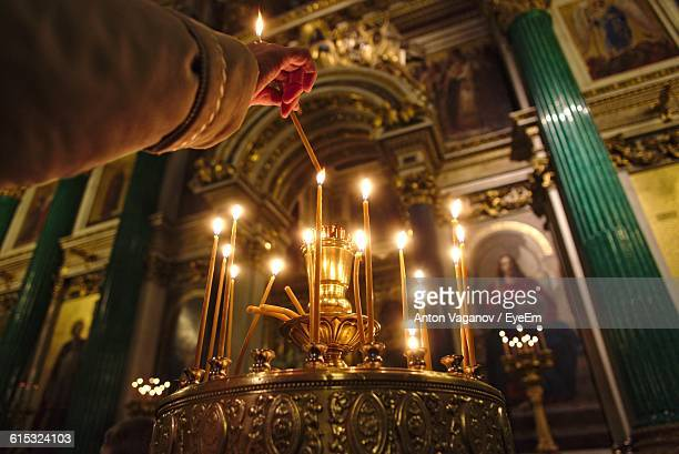 Low Angle View Of Hand Burning Candle In Cathedral During Christmas