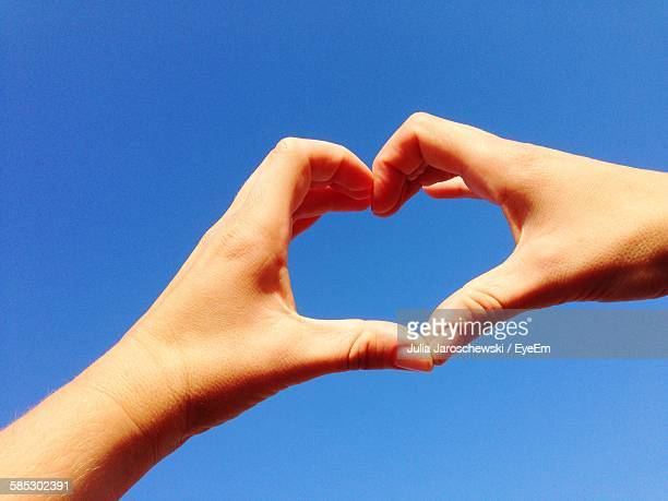 Low Angle View Of Hand Making Heart Shape Against Clear Blue Sky