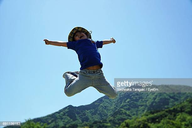 Low Angle View Of Happy Boy Jumping Against Clear Blue Sky