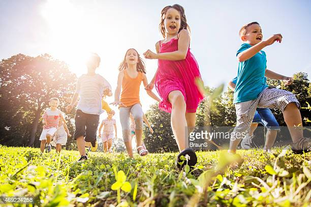 Low angle view of happy children running in nature.