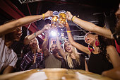 Low angle view of happy friends toasting beer glasses while sitting at table in club