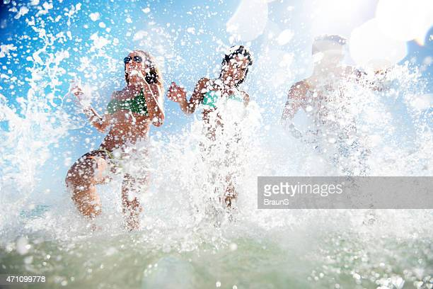 Low angle view of happy people running through the sea.