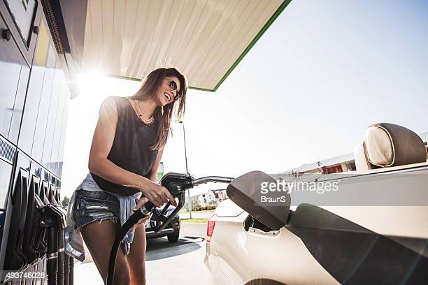 Low angle view of happy woman at gas station.