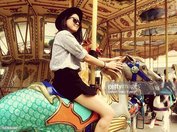 Low Angle View Of Happy Young Woman Sitting On Carousel Horse
