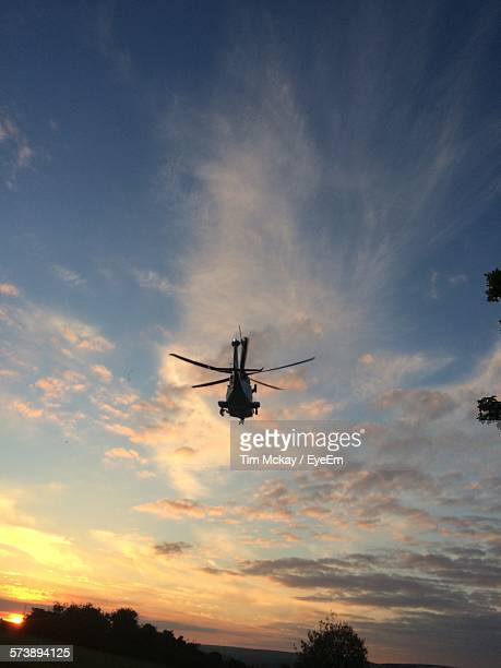 Low Angle View Of Helicopter Against Sky During Sunset