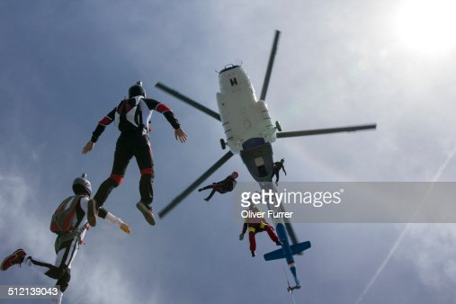 Low angle view of helicopter and six skydivers free falling, Siofok, Somogy, Hungary