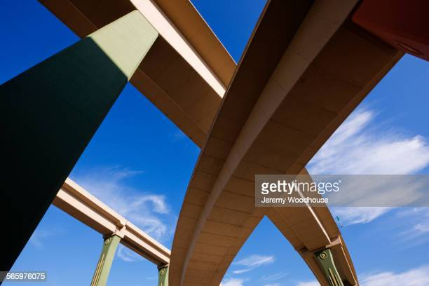 Low angle view of highway overpasses under blue sky