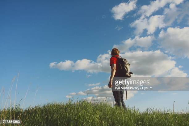 Low Angle View Of Hiker Standing On Grassy Field Against Sky