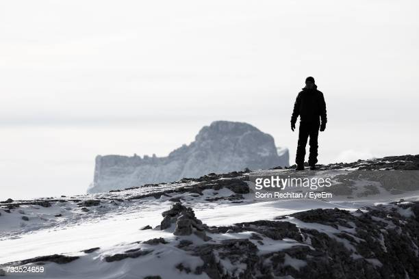 Low Angle View Of Hiker Standing On Snow Covered Mountain Against Sky