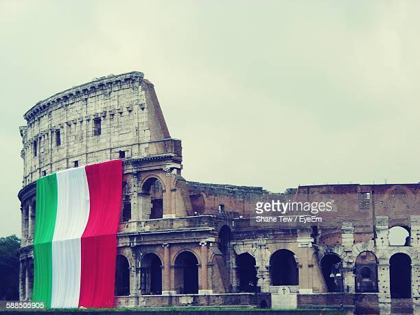 Low Angle View Of Historic Coliseum With Italian Flag Against Sky