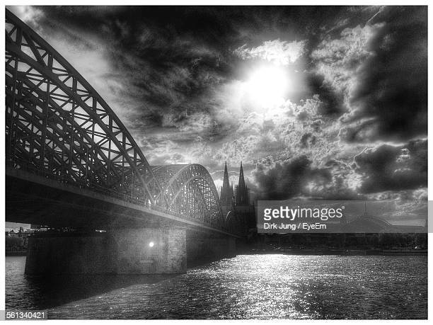 Low Angle View Of Hohenzollern Bridge Leading Towards Cologne Cathedral Over River Against Cloudy Sky
