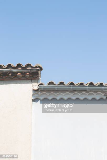 Low Angle View Of House With Tiled Roof Against Clear Blue Sky