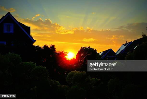 Low Angle View Of Houses Against Cloudy Sky During Sunset
