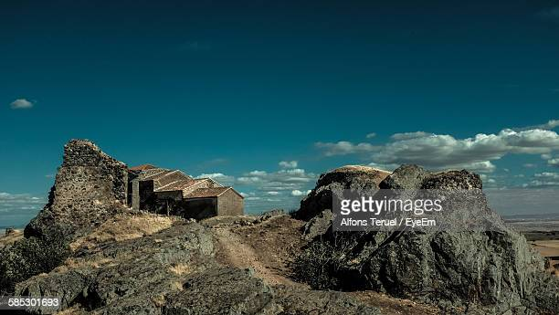 Low Angle View Of Houses And Rocky Mountains Against Sky