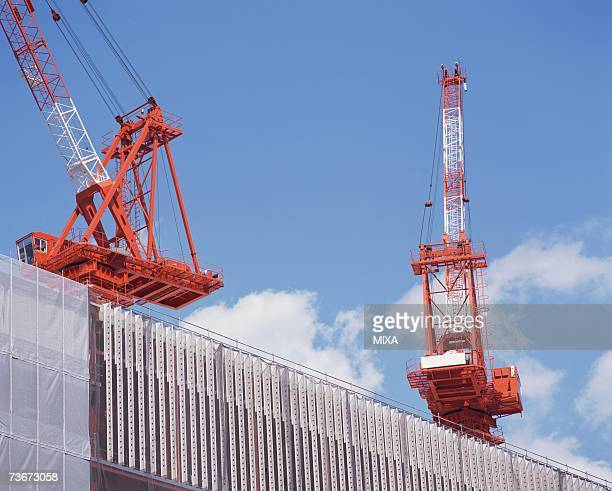 Low angle view of huge cranes at construction site