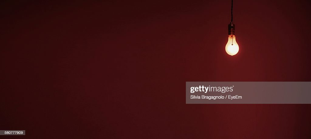 Low Angle View Of Illuminated Bulb Against Colored Background