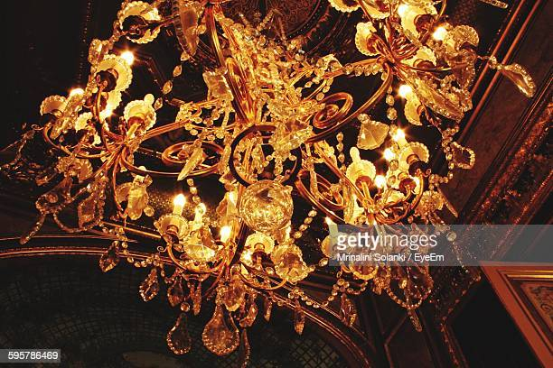 Low Angle View Of Illuminated Chandelier Hanging Against Ceiling