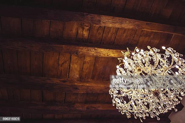 Low Angle View Of Illuminated Chandelier Hanging From Wooden Ceiling