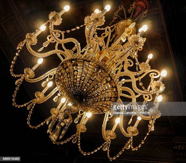 Low Angle View Of Illuminated Chandelier Hanging In Room