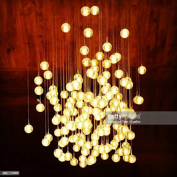 Low Angle View Of Illuminated Crystals Hanging From Chandelier On Wooden Ceiling