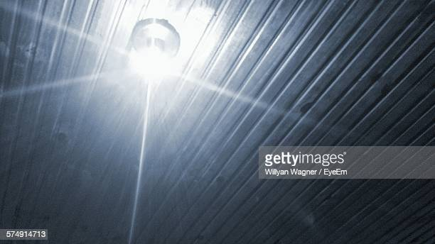Low Angle View Of Illuminated Electric Bulb Against Wooden Ceiling