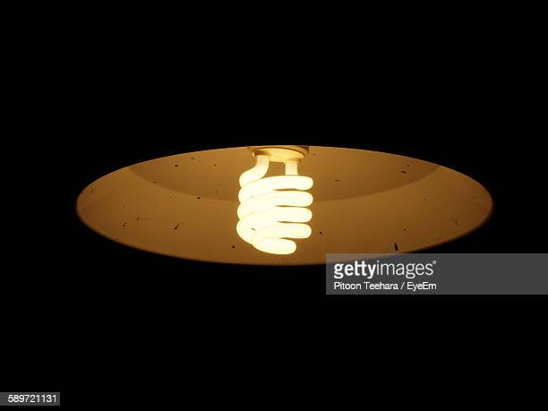 Low Angle View Of Illuminated Energy Efficient Light Bulb In Darkroom