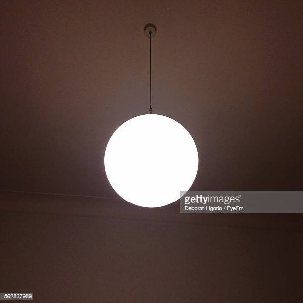 Low Angle View Of Illuminated Lamp Hanging From Ceiling At Home