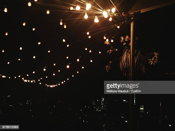 Low Angle View Of Illuminated Light Bulbs Against Sky At Night