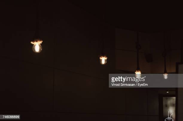 Low Angle View Of Illuminated Light Bulbs Hanging In Room
