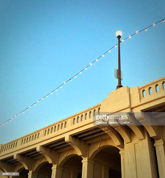 Low Angle View Of Illuminated Lights On Bridge Against Clear Blue Sky