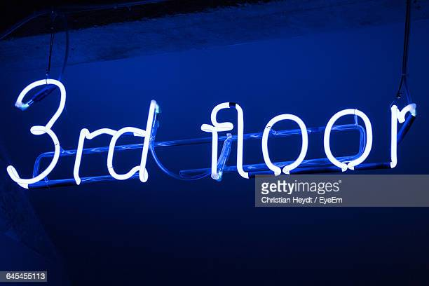 Low Angle View Of Illuminated Neon Sign Against Roof