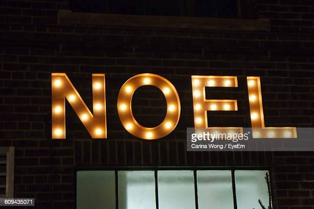 Low Angle View Of Illuminated Neon Sign On Building At Night