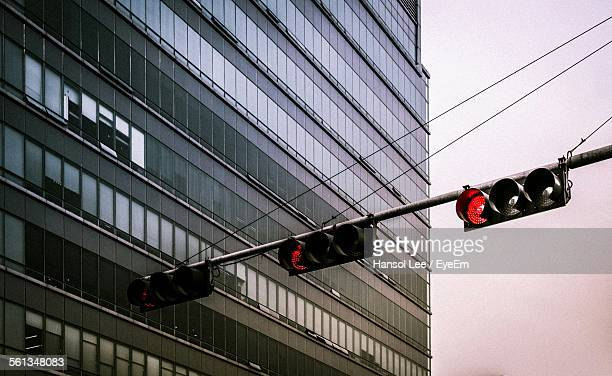 Low Angle View Of Illuminated Road Signal By Building