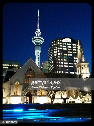 Low Angle View Of Illuminated Sky Tower And Buildings In City At Night